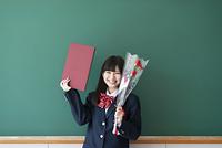 卒業証書と花を持ち微笑む女子学生