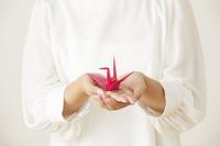 ピンクの折り鶴を持つ手元