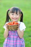 ミニトマトが入っているカゴを持つ日本人の女の子