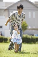 公園で遊ぶ娘と父親