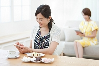 スマートフォン等を操作する中高年女性