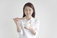 ご飯茶碗を持つ笑顔の日本人女性