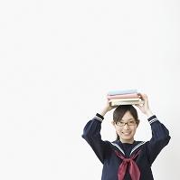 本を頭に乗せる女子高生