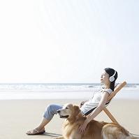 音楽を聴きながら海辺で寛ぐ日本人女性とゴールデンレトリバー
