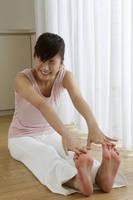 長座体前屈をする女性