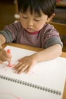 ノートにクレヨンで書く日本人の子供