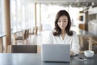 カフェでノートパソコンに向かう女性