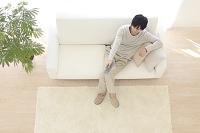 ソファーに座りリモコンを操作する若い日本人男性の俯瞰写真