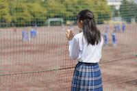防球ネットの側にいる女子中学生