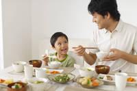 ダイニングテーブルで食事をするパパと男の子