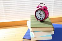 窓際の本の山積みと時計
