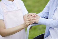 車椅子に乗るシニア女性と介護士の女性の手元
