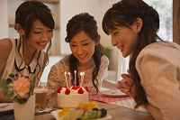 バースデーケーキを見つめる日本人女性