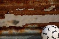 錆びたシャッターの前にあるサッカーボール
