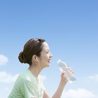 飲料水のペットボトルを持つ日本人女性