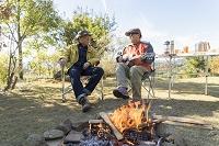 焚き火の前に座るシニアの日本人男性