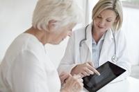デジタルタブレットを用いて、患者にレントゲン写真を見せる医師