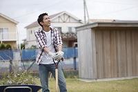 庭仕事をする若者