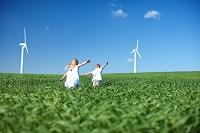 風車のある草原で走る子供たち