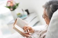 本を読んでいるシニア日本人女性患者