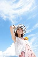 青空の下で帽子を押さえている日本人女性