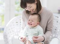 母親の膝に座って笑う赤ちゃん
