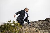 崖を登る日本人ビジネスマン