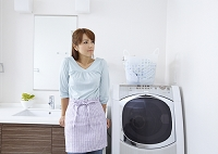 洗濯機の横に立つミドルの日本人女性
