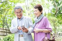 スマートフォンを見る日本人シニア夫婦