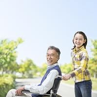 車椅子に乗るシニア男性と女の子