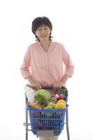 ショッピングカートを押しながら買い物をするシニアの日本人女性