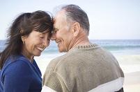 浜辺で笑顔のシニア夫婦