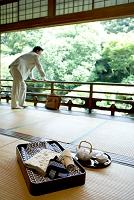 畳の上の葛と茶器と庭をみる日本人男性
