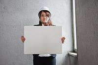 メッセージボードを持つヘルメット姿の女性