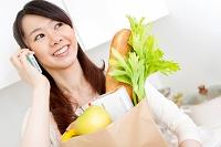 買い物袋を持ちながら電話している日本人女性