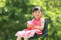 アウトドアチェアに座りドリンクを持つ女の子