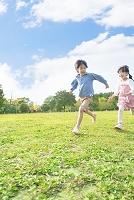 公園を走る笑顔の男の子と女の子