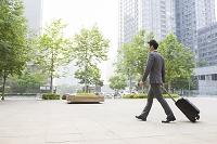スーツケースを引いて歩くビジネスマン