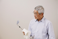 ゴルフのアイアンを磨くシニアの日本人男性