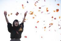 落ち葉を撒く日本人女性
