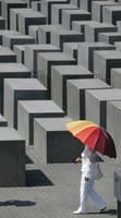 ホロコースト記念碑で傘を差す女性