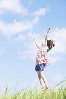 手を伸ばしてジャンプする日本人の女の子