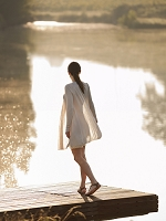 水辺に立つ外国人女性の後姿