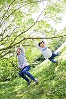 公園で木の枝にぶら下がる姉と弟