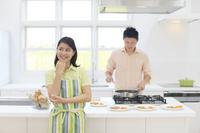 明るいキッチンで料理をする男性と考える女性