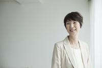 窓ぎわに立つミドル日本人女性