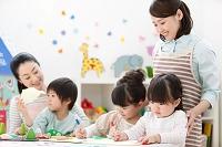 絵を書く園児と保育士