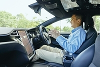 自動運転の車に乗る日本人男性