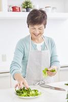 サラダを盛り付ける日本人のシニア女性