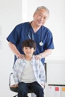 座っている男の子と医師